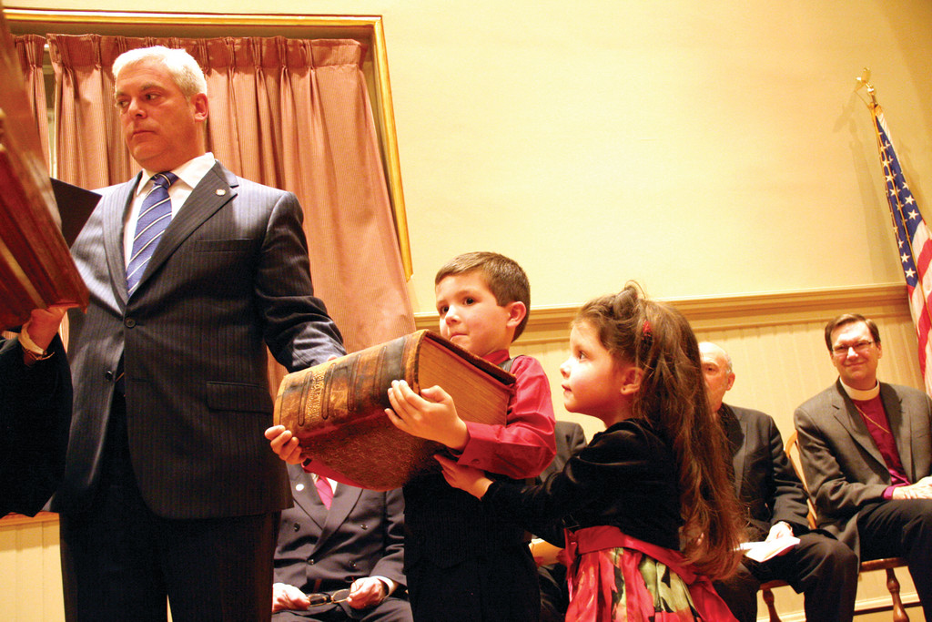 Jacob and Isabel Butts hold the Bible that's almost as big as they are as Mayor Scott Avedisian is sworn in at Tuesday night's Inauguration Ceremony at City Hall. At least 400 people were in attendance.