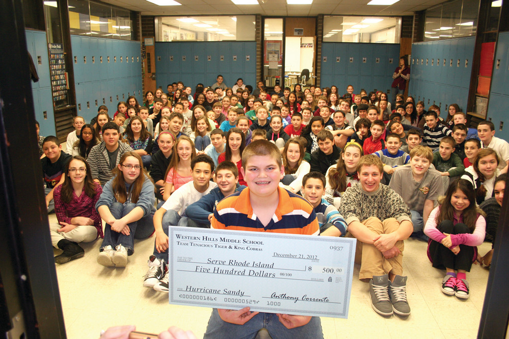 A GIFT FROM US: Tyler Lopez poses with a check for $500 in front of his seventh grade classmates on the Tenacious Tigers and King Cobras teams. Lopez proposed the fundraiser to benefit local victims of Sandy.
