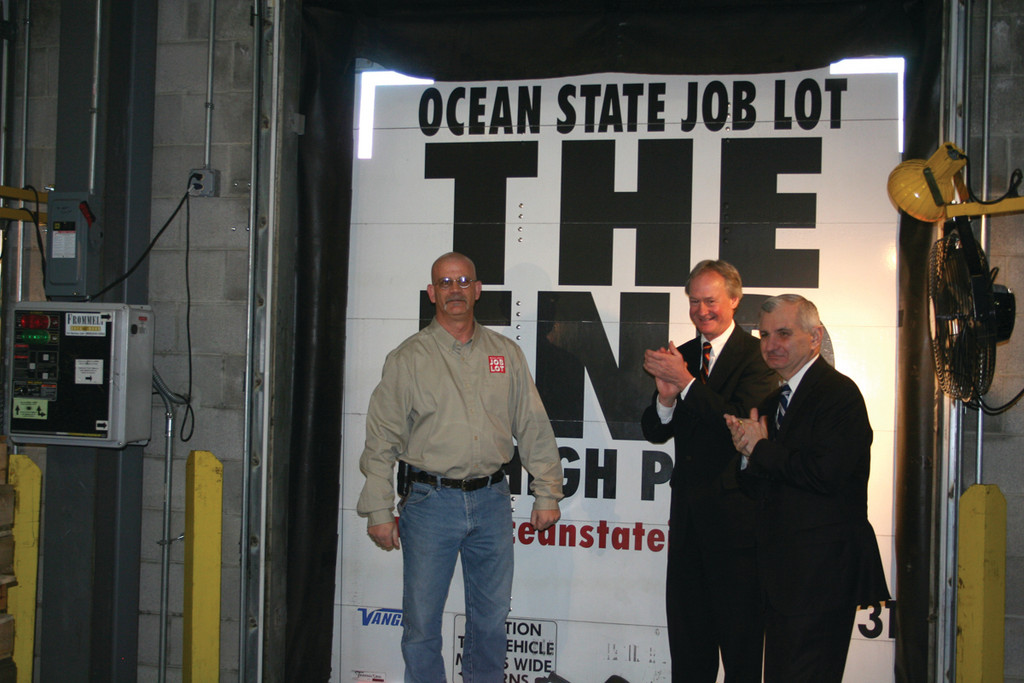 MOVE THAT TRUCK: In the OSJL Quonset warehouse, Governor Chafee and Senator Reed help a company employee close the back of a delivery truck that was headed to one of 10 regional food banks.