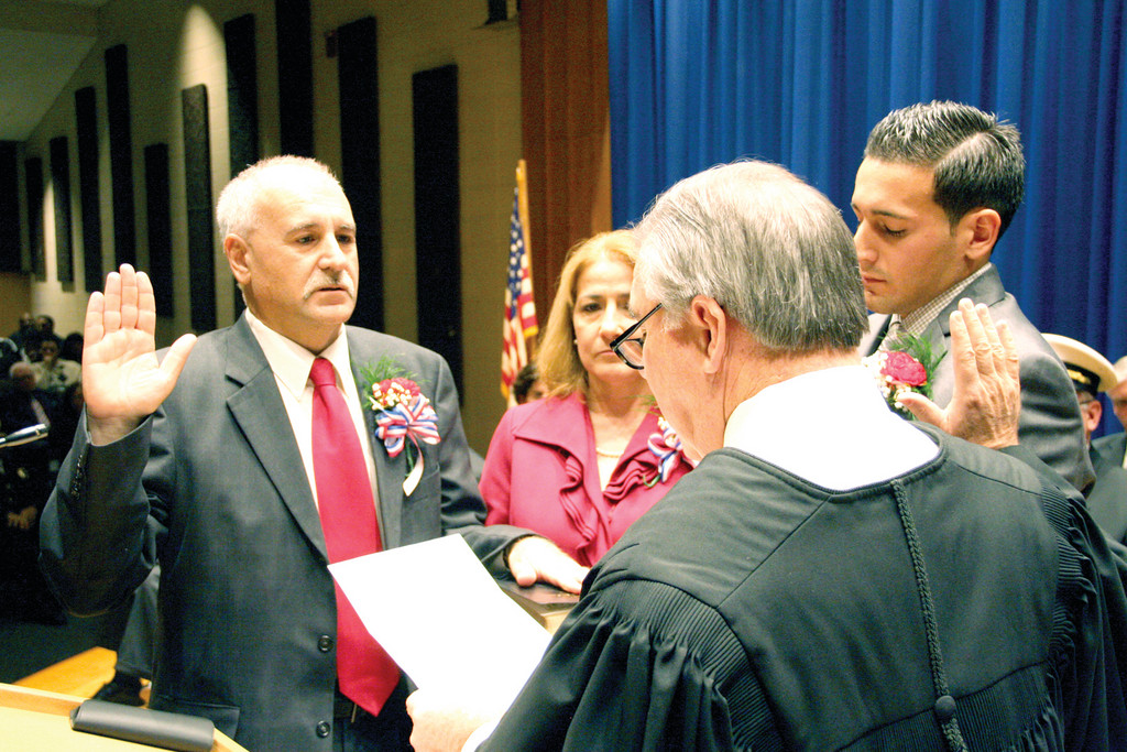 Mayor Joseph Polisena takes the oath of office from the Honorable Francis Flaherty, as his wife, Lucy, and son, Joseph Jr., look on at Monday's inauguration ceremony held at Johnston High School.