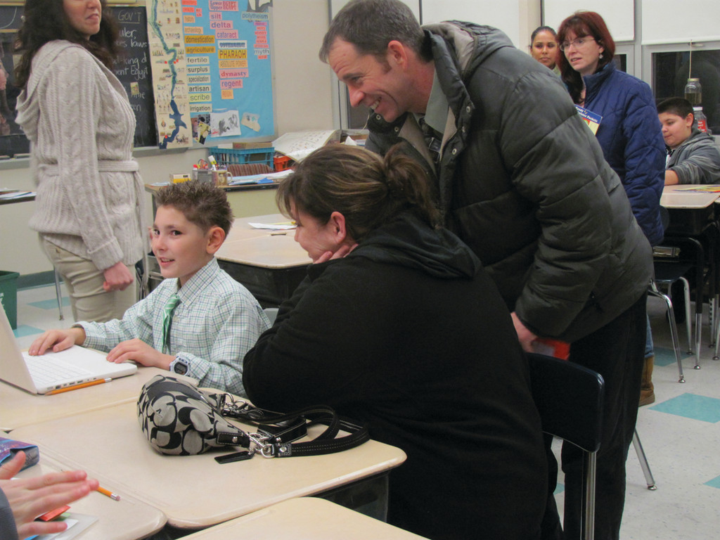 Lucas Patrone (left), a sixth grader at Ferri, shows Jackie Blakney and Chip Crowley his computer game.