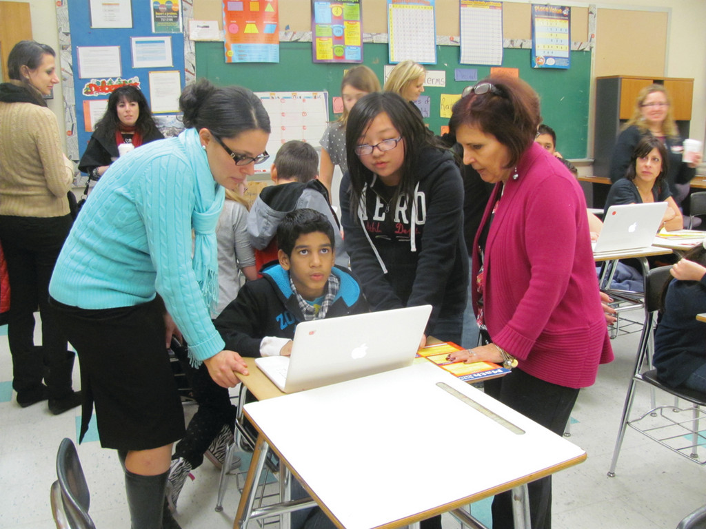 Leanne DeMarco (left), the assistant principal at Ferri Middle School in Johnston, looks over a computer station manned by seventh grader Giovanni Colon during Tuesday night's Family Math Night at Ferri. Looking on is sixth grader Maikou Kue and teacher Christine Murphy, who helped coordinate the event.