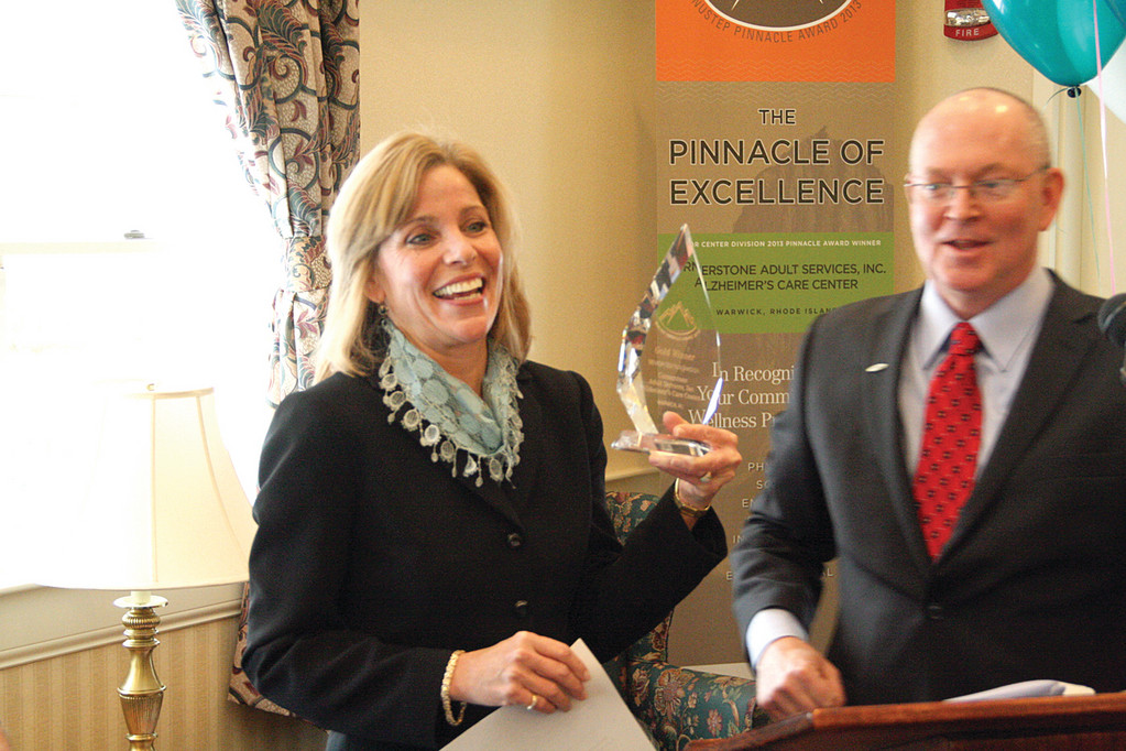 AT THE TOP: Cornerstone Adult Services Administrator Dottie Santagata holds the Pinnacle Award aloft as NuStep's Steve Sarns looks on during yesterday's ceremony.