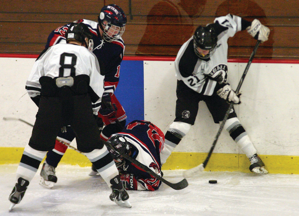 PUCK WATCH: Pilgrim's Liam Strain tries to break the puck out of a scramble on the boards during Sunday's game.