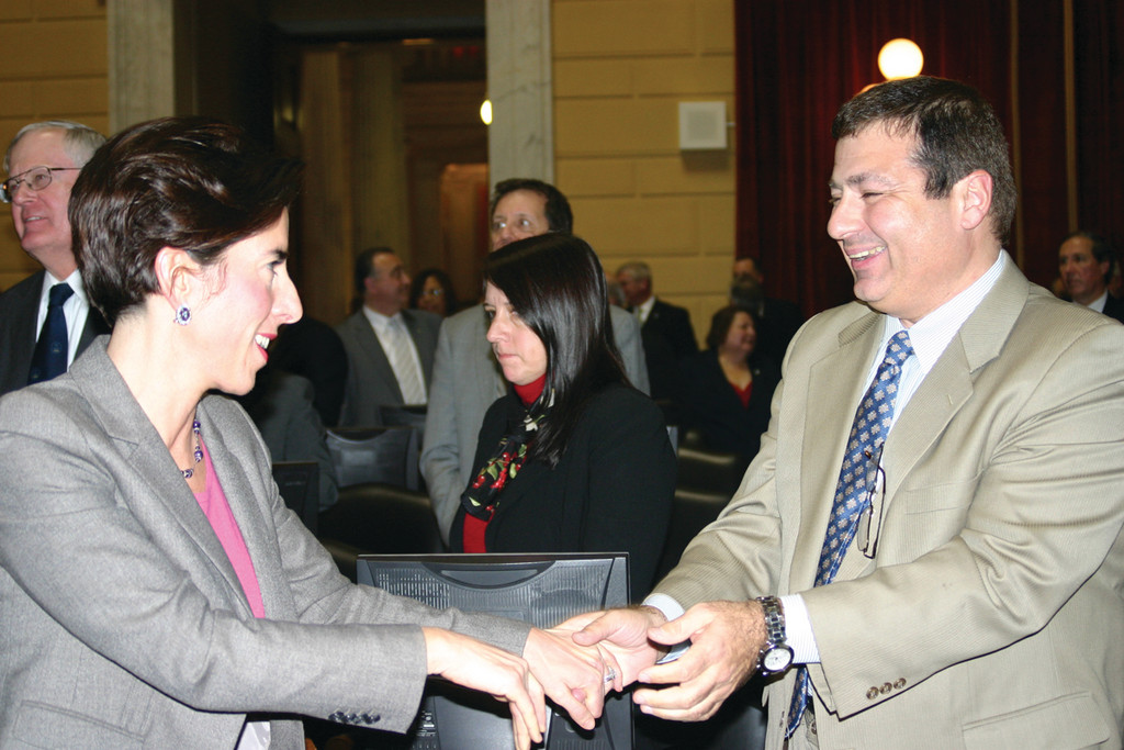 OLD PALS: General Treasurer Gina Raimondo and Warwick Representative Joseph Shekarchi hold hands after embracing at Wednesday's State of the State address in the House Chambers of the State House. Shekarchi, who is serving his first term as a State Rep, worked as Raimondo's campaign manager in 2010.