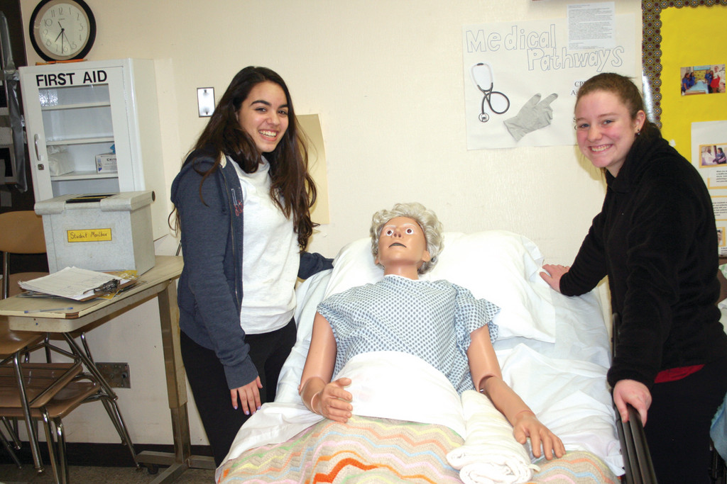 A PATIENT PATIENT: Alyssa Bailey and Brittany McSparren pose with one of the manequins used in the Medical Pathways program where students are taught proper techniques for handling patients during medical procedures.