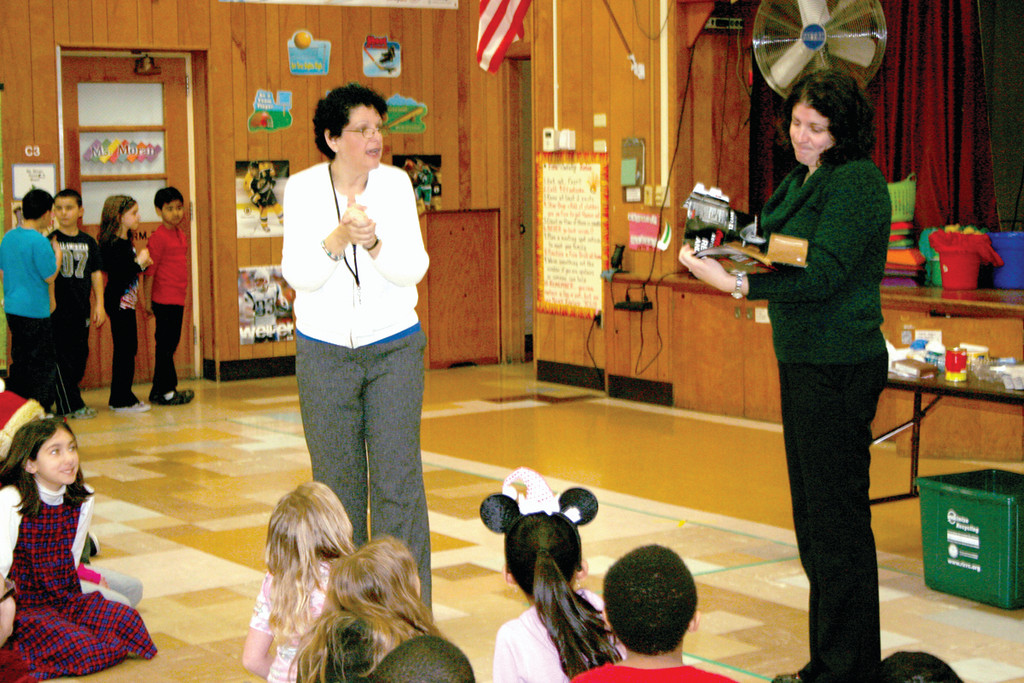 IS IT OR ISN'T IT: Danielle DeSimone, fifth grade teacher at Glen Hills, tries to determine whether or not a cardboard box from a case of soda is recyclable or not. Due to the chemical coating sprayed on the cardboard, the item was not recyclable.