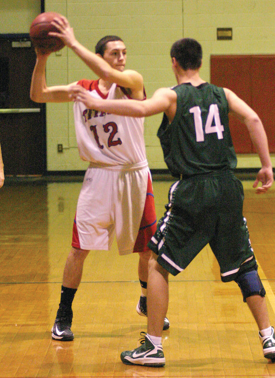 HOLDING OUT: Ben Mann lifts the ball high while being guarded on the perimeter.