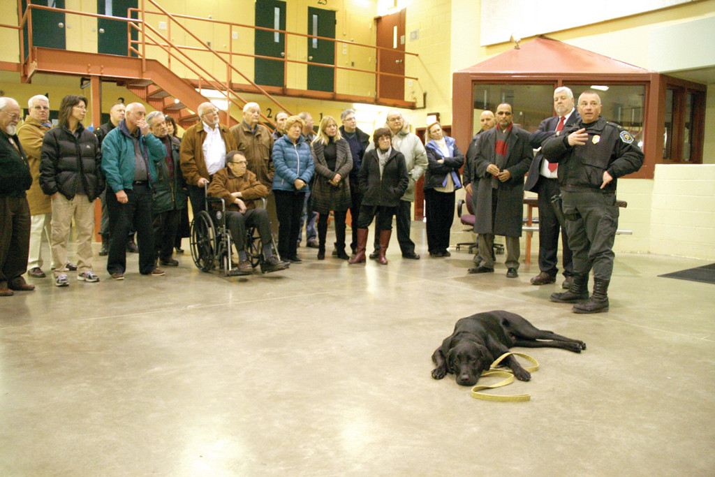 ACCUSTOMED TO CROWDS: A black lab, being trained to work with the disabled under the NEADS program, seemingly is oblivious to a group of Warwick Rotarians as an inmate, not pictured, describes the rewards of working with the dog.
