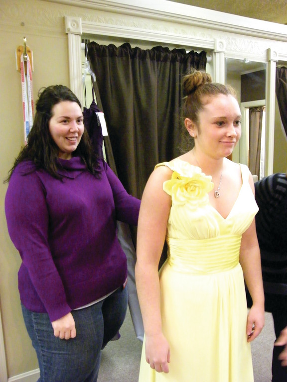 BRIDESMAID FITTING: Kelly Shaw, who will get married to her fiancé, Chris Bennett, next winter, helps her bridesmaid and future sister-in-law, Lindsey Bennett, try on her bridesmaid dress.