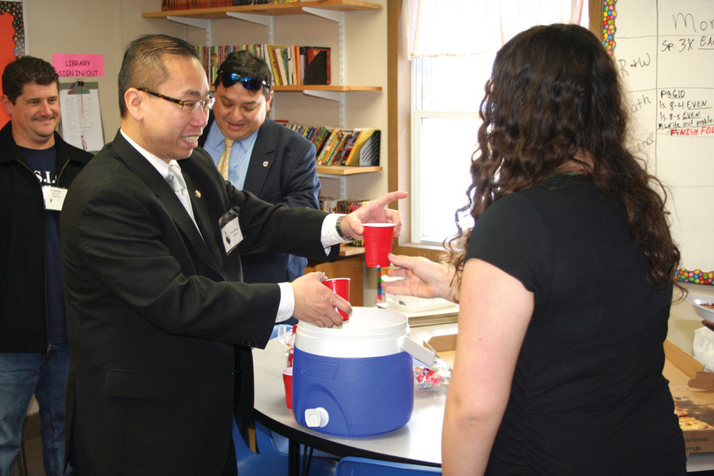 JUICE ANYONE? Mayor Fung serves juice to the students during their lunch at Woodridge School recently.