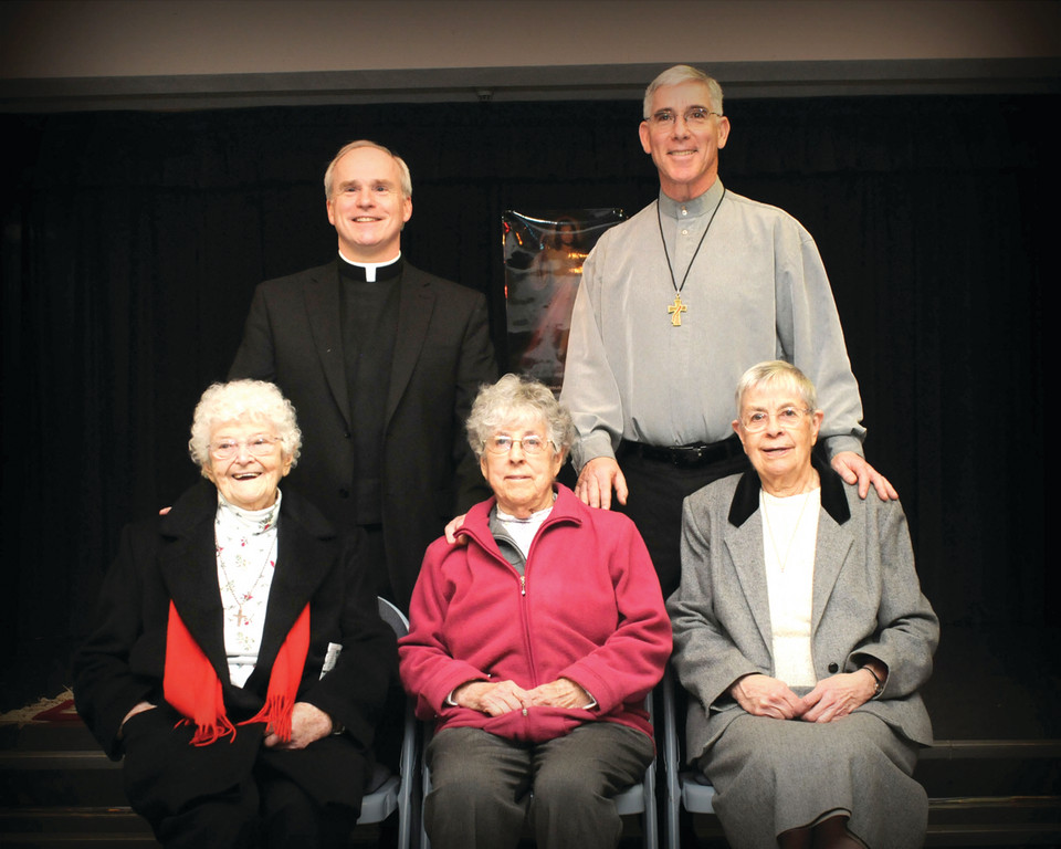 FOND FAREWELL: SS. Rose and Clement Parish bids farewell last week to three religious sisters from the Congregation of Notre Dame. Seated from left to right are: Sr. Marie Cafferty, Sr. Rita McGetrick and Sr. Simonne Camire. Standing is the parish's pastor, Fr. Edward Wilson Jr. (left), and the parish deacon, Noel Edsall.