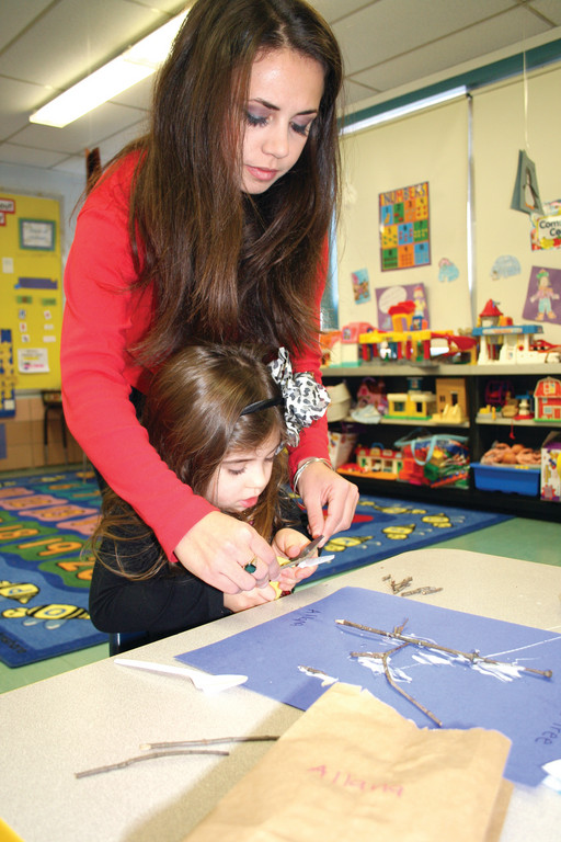Allesandra DiOrio helps Allana Bibby with her fine motor cutting skills.