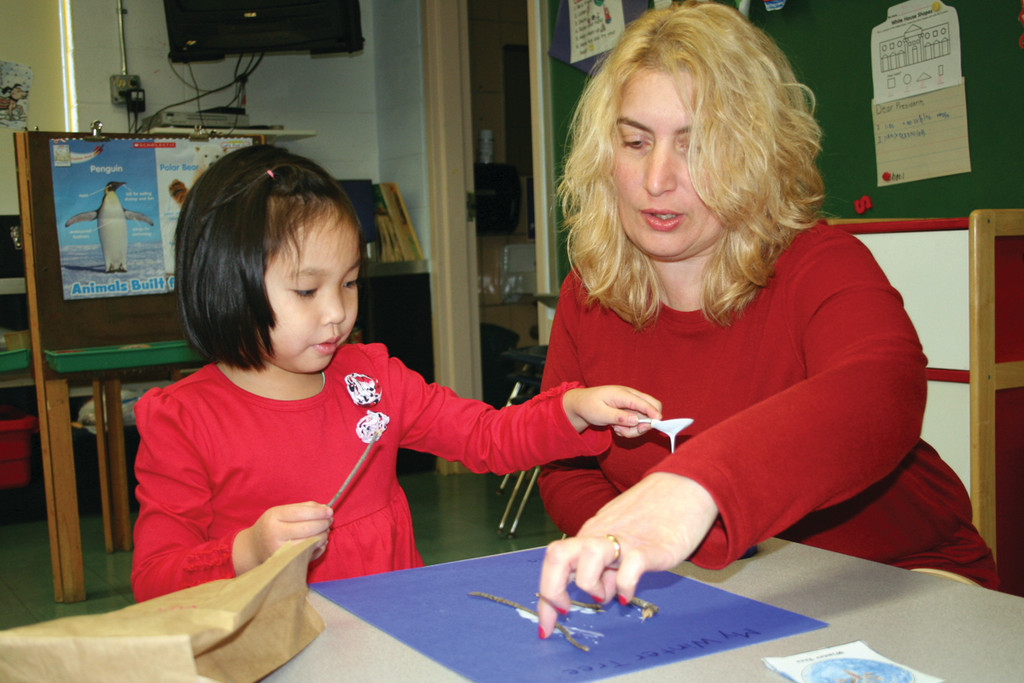Pre-K Teacher Assistant Elizabeth Rocchio helps Minna Lin with her project.