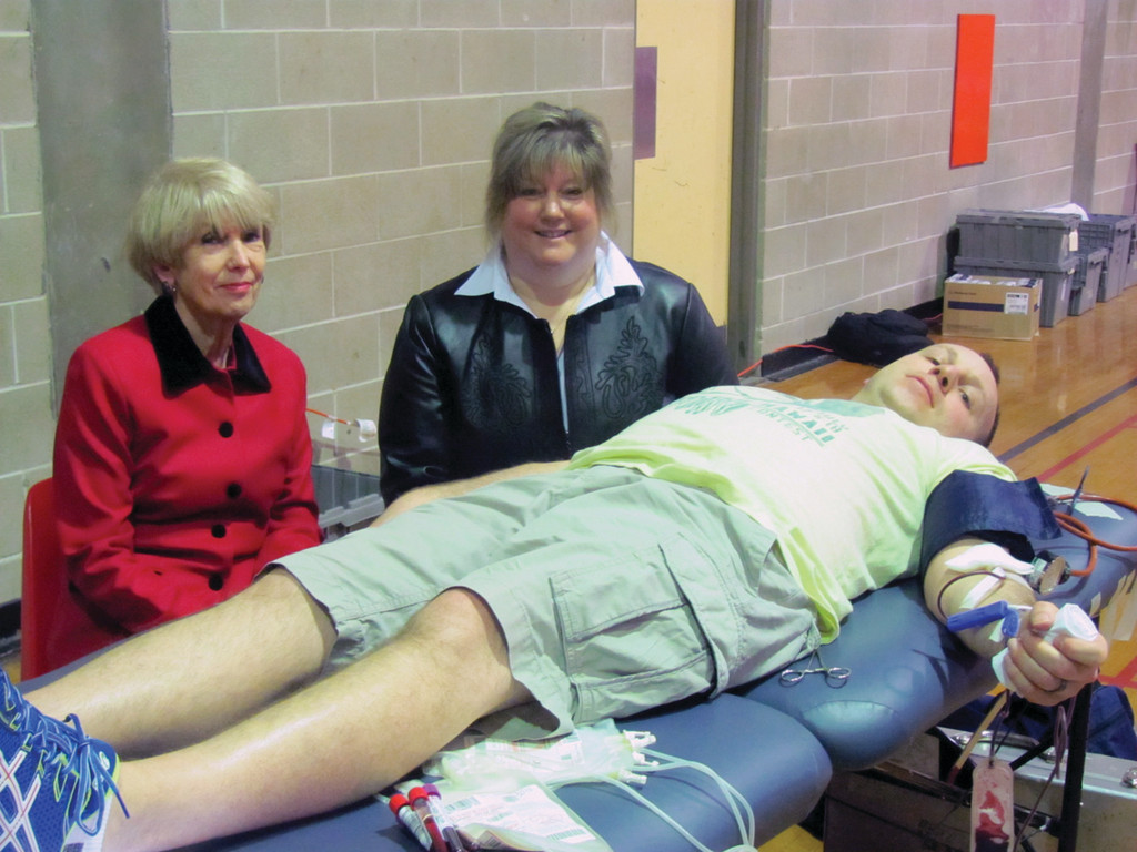WHAT A PARTY: Bill Russo, a physical education teacher and coach at Toll Gate High School, lies on a Rhode Island Blood Center table while giving blood in honor of Candace Calouri, the school�s assistant principal who yesterday celebrated her first birthday with a new kidney. She�s joined by her mother, Cynthia Calouri.