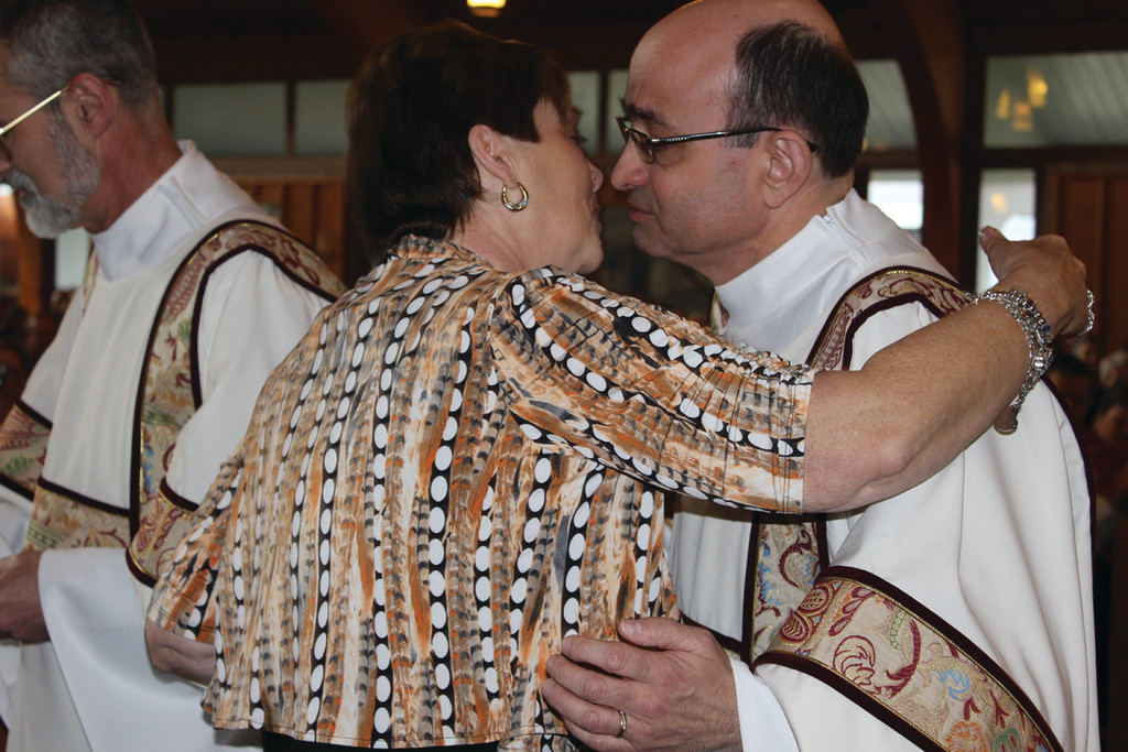 WITH LOVE... After blessing a silver necklace adorning the Blessed Mother and presenting it to his wife, Helen, Deacon Andrade leans in for an embrace.