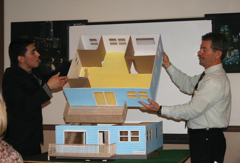 FROM ONE FLOOR TO TWO: Jamie Barrio's model is a two-floor model. Here, Rich Lonardo helps him remove the second floor so that guests can see both the first and second floor models.
