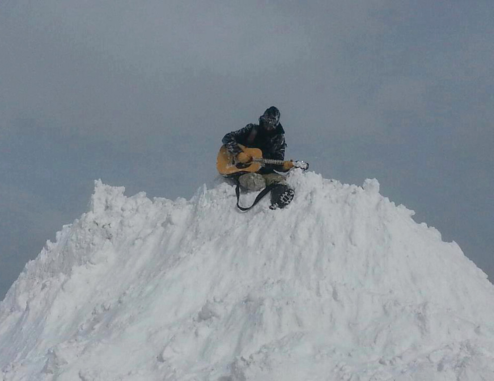 IN TUNE: A local man plays guitar atop a snow bank off Main Avenue.