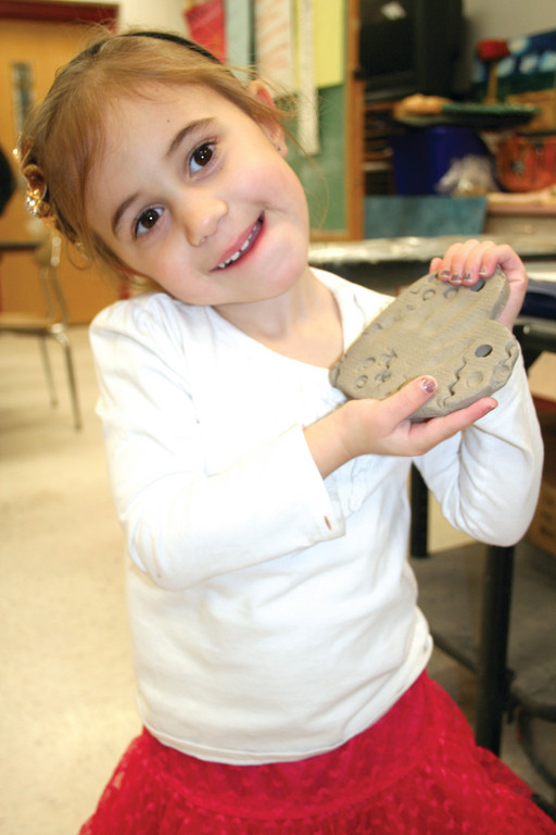 MY HEART BELONGS TO DADDY: Mia Moretti shows off the ceramic heart she made in art class for her father's platoon.
