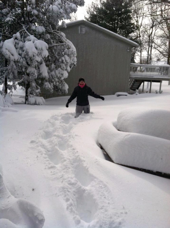 IN THE THICK OF IT: Cranston resident Michele Dunphy Giardina wades out in her backyard, thigh-deep in snow.