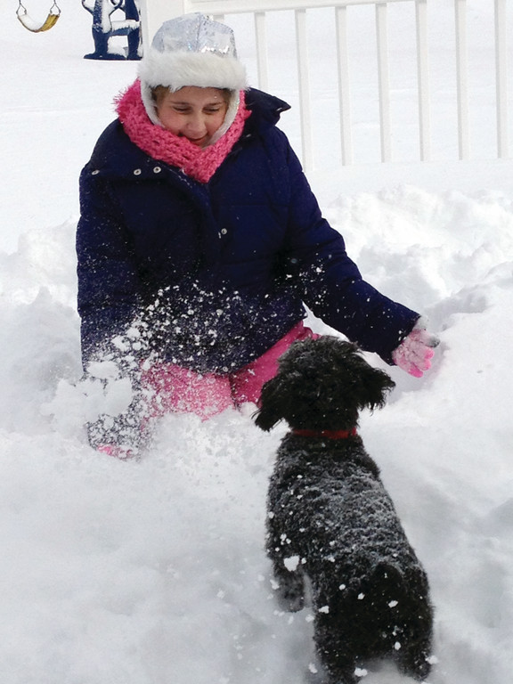 WINTER FROLIC: Kaylyn Zayat plays in the snow with her dog, Teddy.