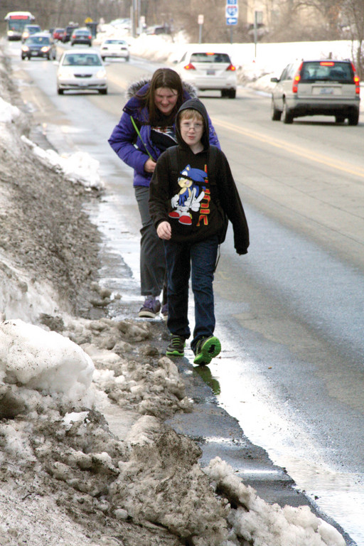 NOWHERE TO GO BUT THE STREET: Allyson Spencer, a student at Toll Gate, and her brother, Justin, who is a student at Winman, are forced to walk in Toll Gate Road Tuesday on their way home from school.
