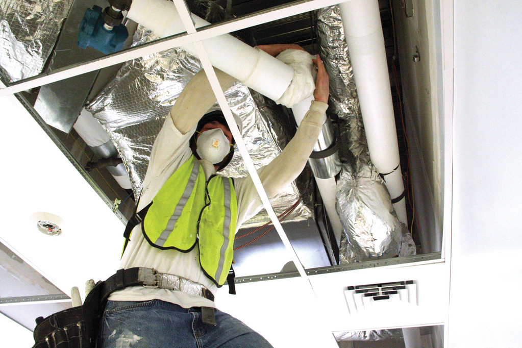 IT'S A WARP: Tony Kilcullen wraps steam pipes with insulation.