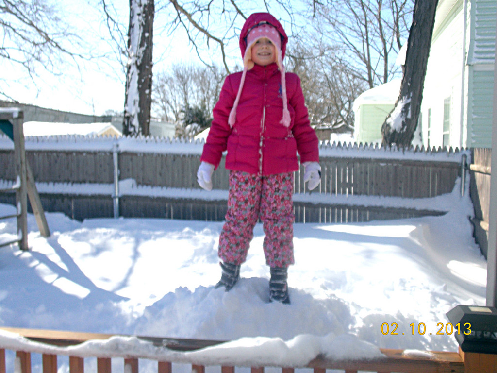 Ready to tackle the snow, 7-year-old Gianna Halliwell climbs a snowdrift in her backyard in Johnston.