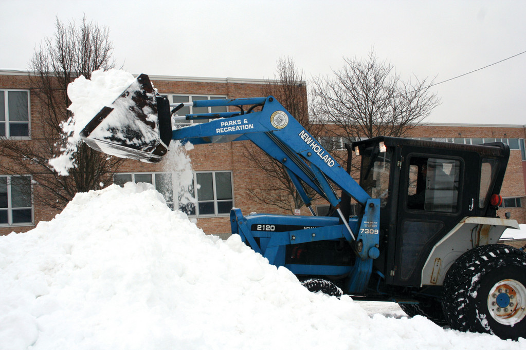 Plows clean out the Johnston High School parking lot.