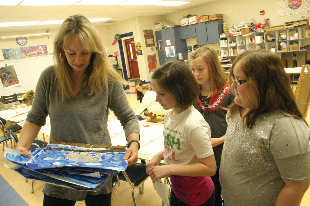 HELPERS AT HER SIDE: Arts teacher Kim Markarian gets some help in setting up a class for Hoxsie School second graders from Deirdre McCaffrey, August Allaire and Kristina Elinwood, all fourth graders.