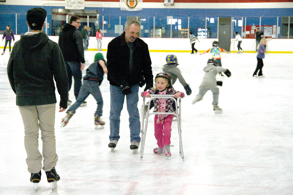 ENCOURAGEMENT: Tony Gomes lends a helping hand to six year old Hannah Greene, who is learning to skate.