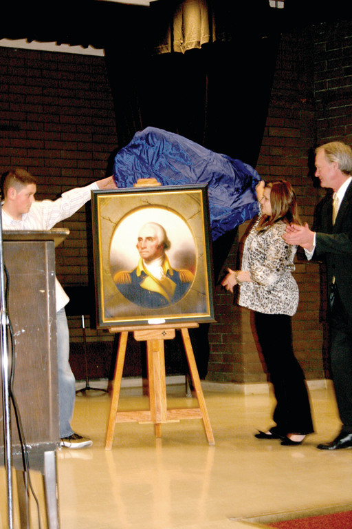 THE UNVEILING: Zach Pickering and Bella Connors assist Governor Lincoln Chafee in the official unveiling of the portrait of George Washington, which will hang in Western Hills Middle School.