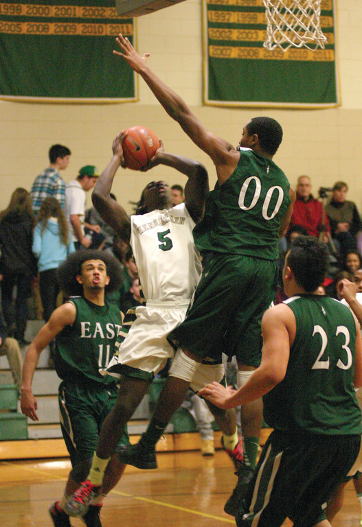 Karze Cummings tries to take a shot with East's Marven Beauvais bearing down on him.