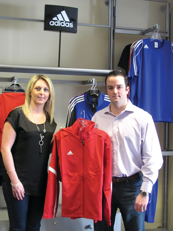 FAMILY FUNCTION: The husband and wife team of Tiffany and Drew Omicioli are among the executive management team of now Warwick-based Squadlocker. The couple, who starred in collegiate ice hockey at UConn and Providence College respectively, hols an Adidas jacket inside the well stocked retail store at 240 Bald Hill Road in Warwick.
