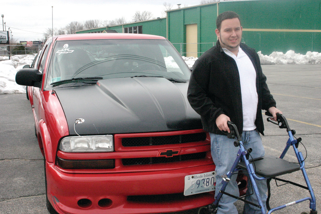 DRIVING TOWARD SUCCESS: Being disabled doesn�t stop Coventry resident Tyler Hittner from pursuing his dreams, as he operates a detailing business out of The Battery Shop on Post Road. Here, he stands with his beloved Chevy S10.