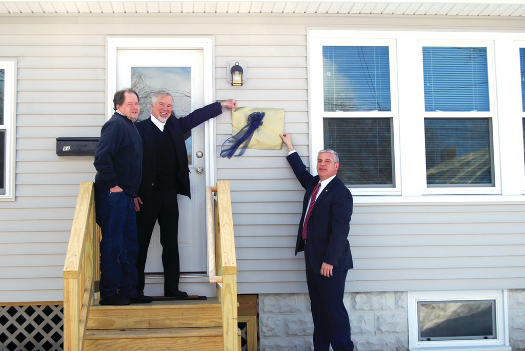 KEEPING IT AFFORDABLE: Ed Rouse, who lives in the house on Benedict Road, is joined by David Lauterbach of The Kent Center and Mayor Scott Avedidian at an unveiling of a plaque on the building that has been renovated with city funds.