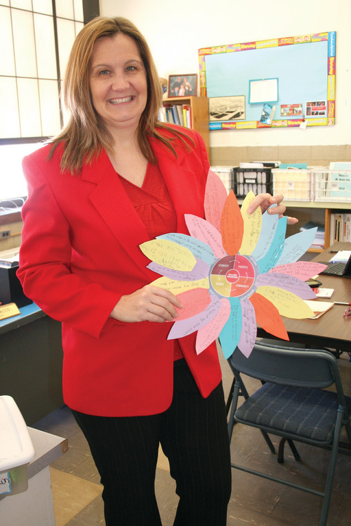 SIGNS OF SPRINGTIME: Principal Cherie Sacco holds up one of the school-wide projects undertaken during Michele Theroux's Kindness Week. Each classroom created a flower using one petal from each student in the class, focusing on acts of kindness. The flowers will be on display at Stadium, showcasing the students' good deeds.