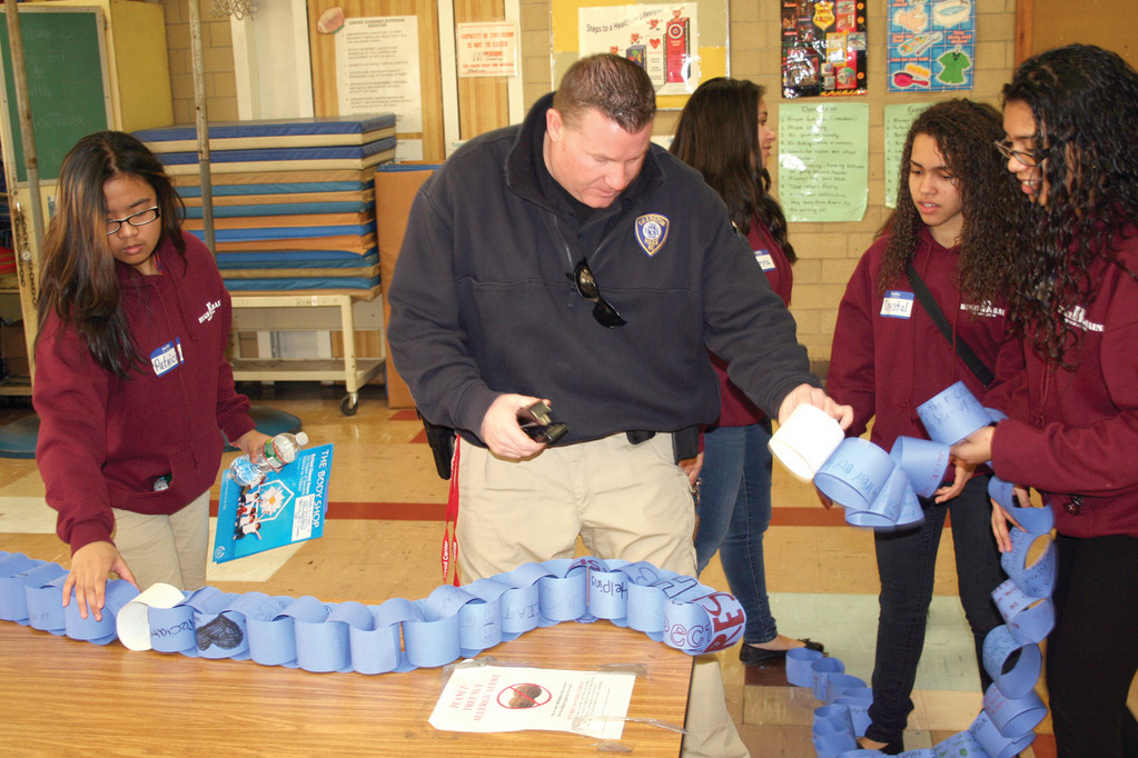 KEEPING THE CHAIN GOING: School Resource Officer Kevin Denneny helps Bain students Patricia Lasala and Crystal Gonzalez put each classroom's links together to form a school-wide chain of kindness and good deeds.
