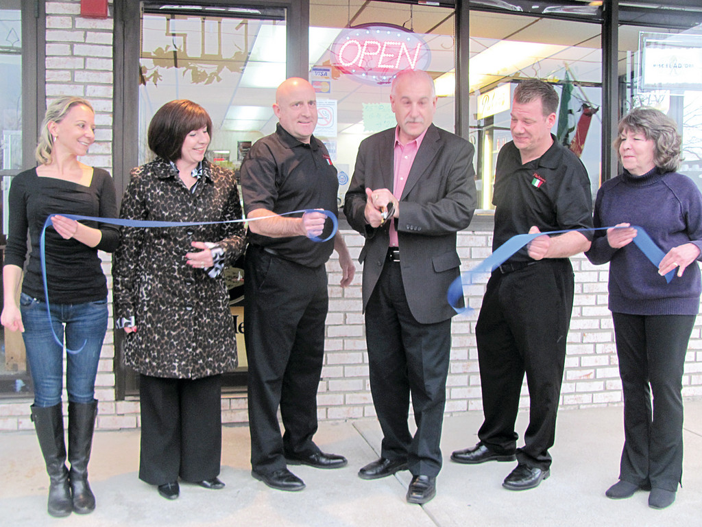 Johnston Mayor Joseph Polisena performs the traditional ribbon cutting ceremony at Palermo Salumeria Italiana, which has only been open a few months but is already receiving rave reviews. Taking part in Tuesday's event were, from left, cook Lisa Grasso, NCCC President Deborah Ramos, co-owners Scott Partridge and Brad Lo Verde and Kathleen Lo Verde.