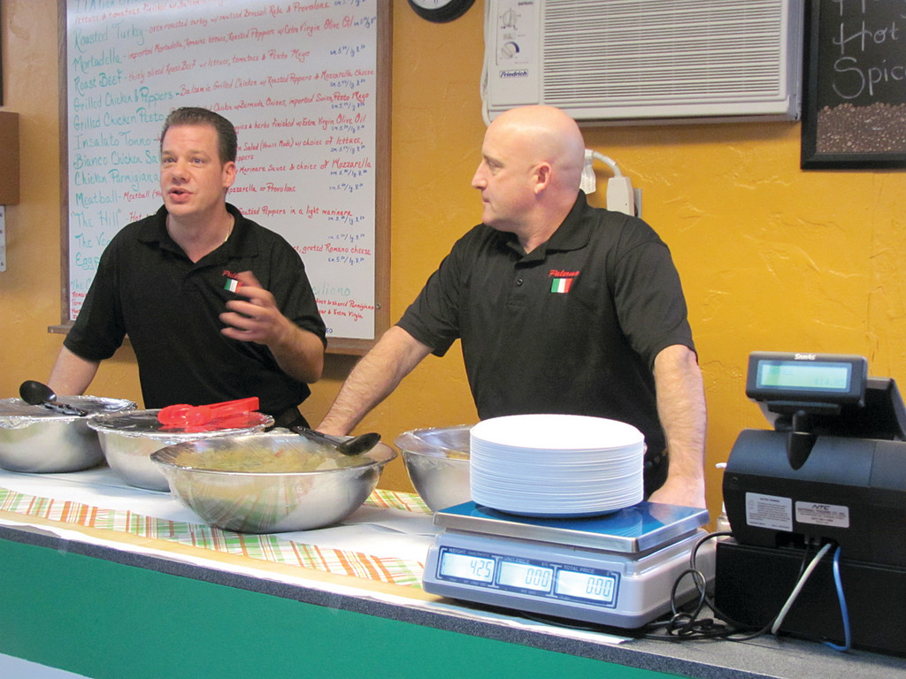 Owners Brad Lo Verde and Scott Partridge explain different dishes on their menu to people who attended Tuesday's ribbon cutting in Johnston.