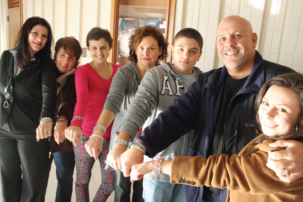 Tabz-4-Tomorrow bracelets are displayed by Kendra Cimaglia and members of her family during the Metta Students Foundation presentation in November of 2012. From left are Wendy Giorgio, Laurie Aydet, Kendra, Kerry Cimaglia, Nick Cimaglia, Tony Cimaglia and Kailyn Audet.