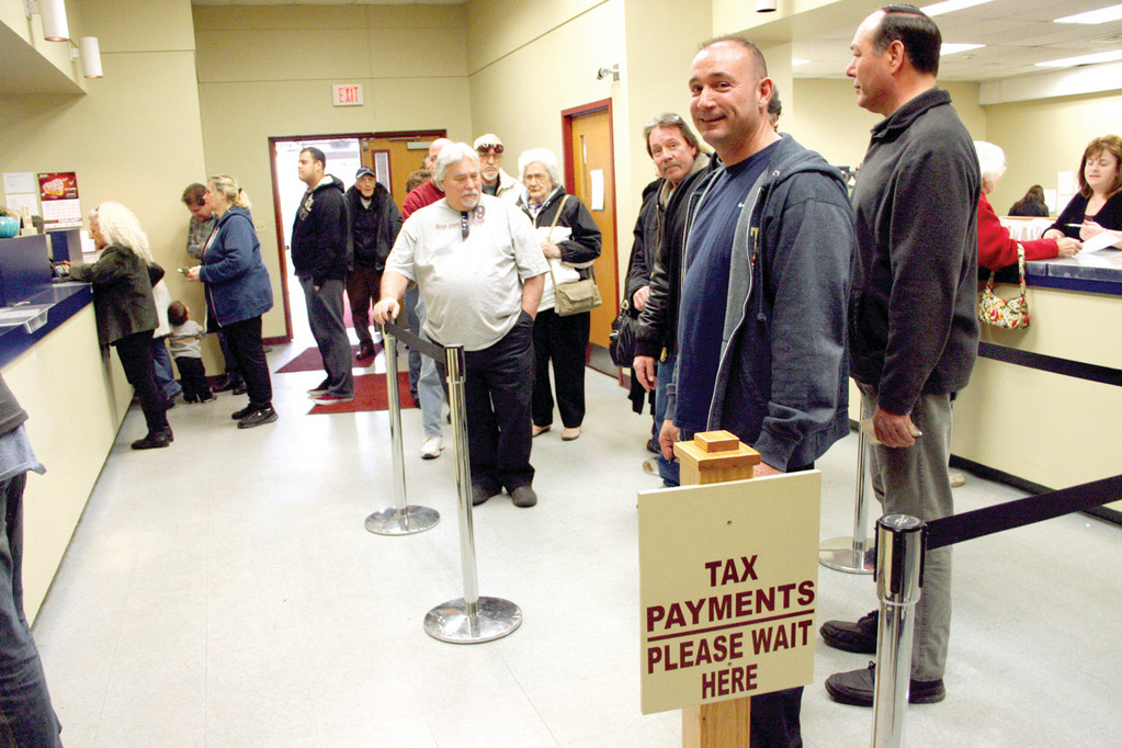 IN THE SLOW LANE: Motor vehicle owners line up to pay their taxes Friday at the City Hall Annex.