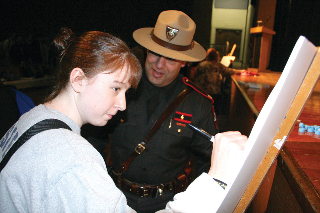 Signing the pledge, as Major David Tikoian of the State Police looks on, is Allie Ryan.