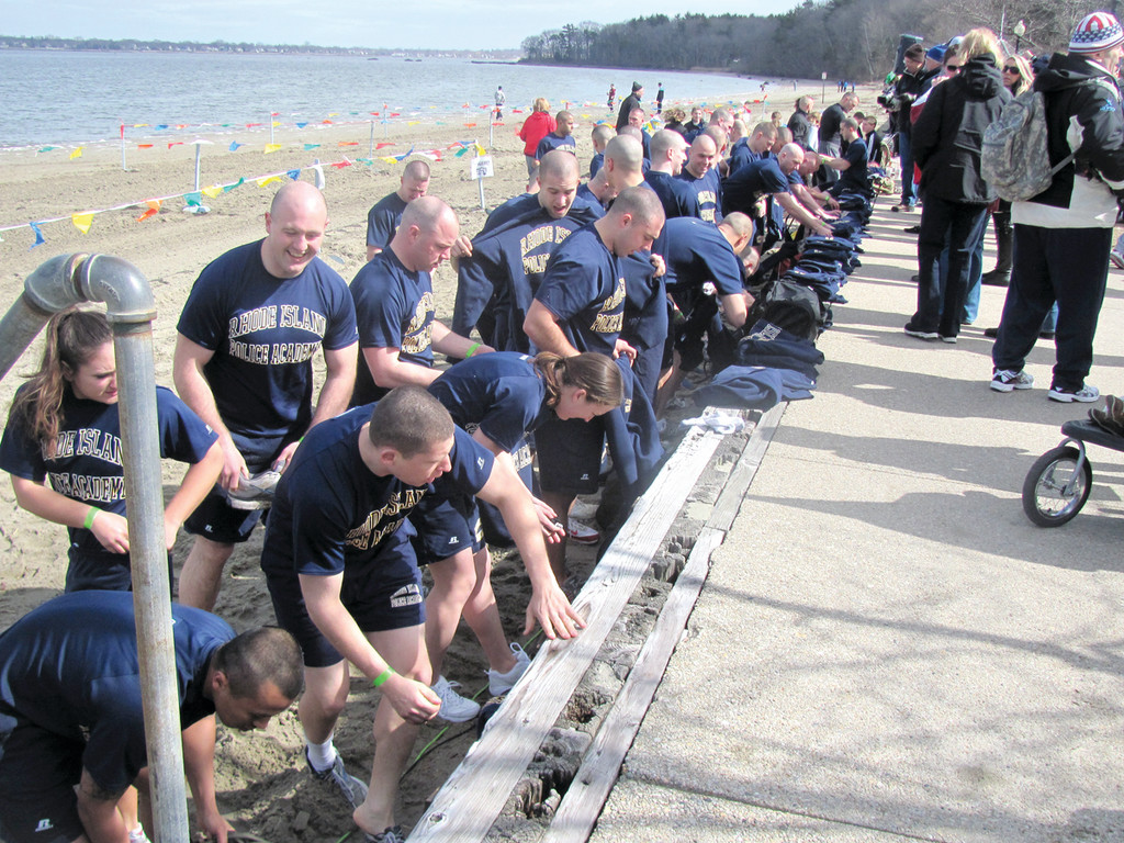 DIFFICULT DUTY: These are some of the many members of the Rhode Island Police Training Academy that exercised on the beach at Goddard Memorial State Park Sunday prior to the sixth annual Torch Run Plunge. The officers-to-be completed their workout and went dashing into the frigid waters.