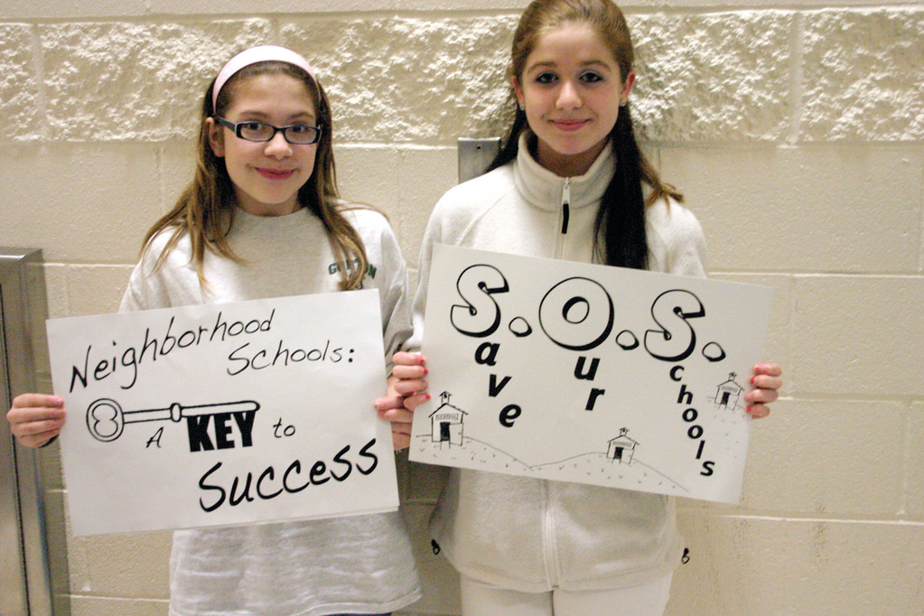 SAVE OUR SCHOOL: Gorton seventh graders Alanna Morrison (left) and Julia Dutra hold signs advocating to save their school from closing.