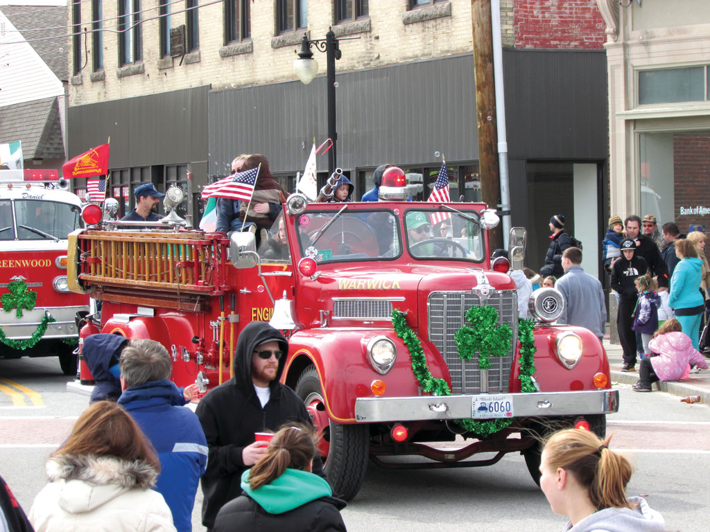 RED DRESSED IN GREEN: The Greenwood Fire Company drove their vintage truck along the parade route in the sixth and final division, featuring trucks from area fire companies.