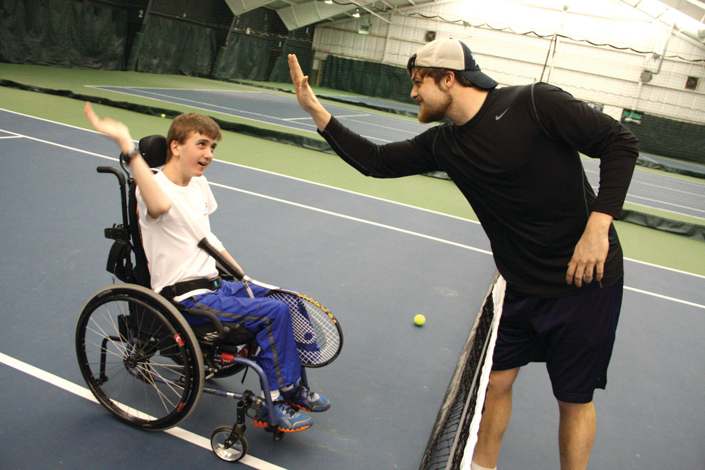 SERVING UP A SMILE: Andrew Martin receives an enthusiastic high-five from his coach, Tait Ehrenclou, following his wheelchair tennis lesson at Tennis Rhode Island in Warwick.