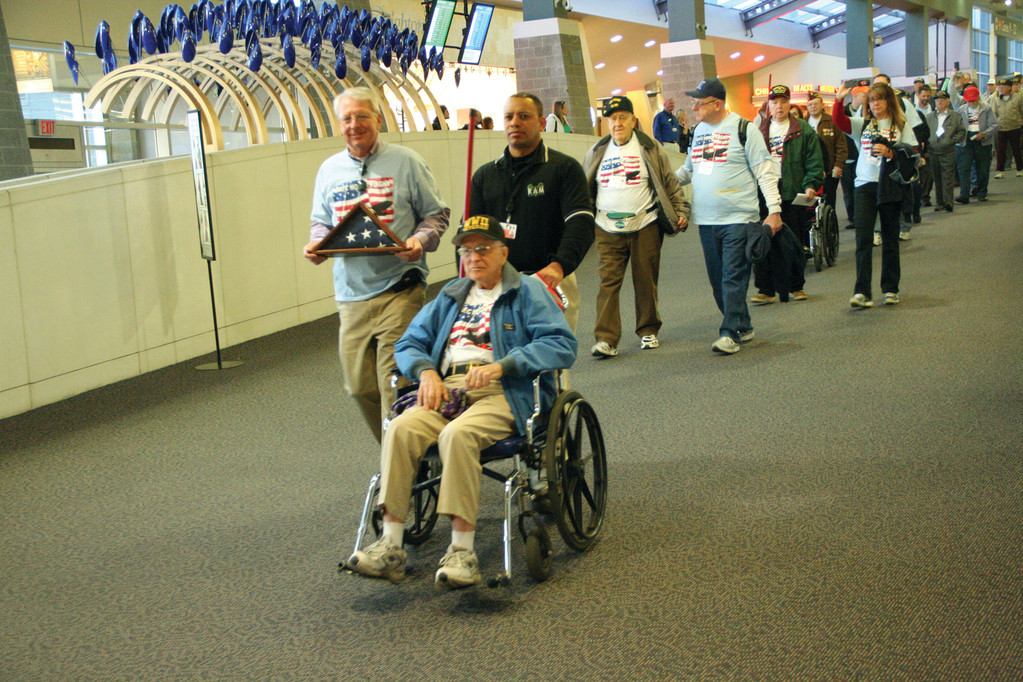IN THE LEAD TO DC: WWII vet Louis Algier and his guardian leads other vets and their escorts as the groupheads for their flight.