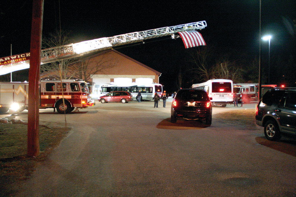WELCOME LADDER: This was the scene around 5:30 last Saturday morning at the Warwick Fire Department on Post Road. Above, an aerial truck displays Old Glory amid spotlights.