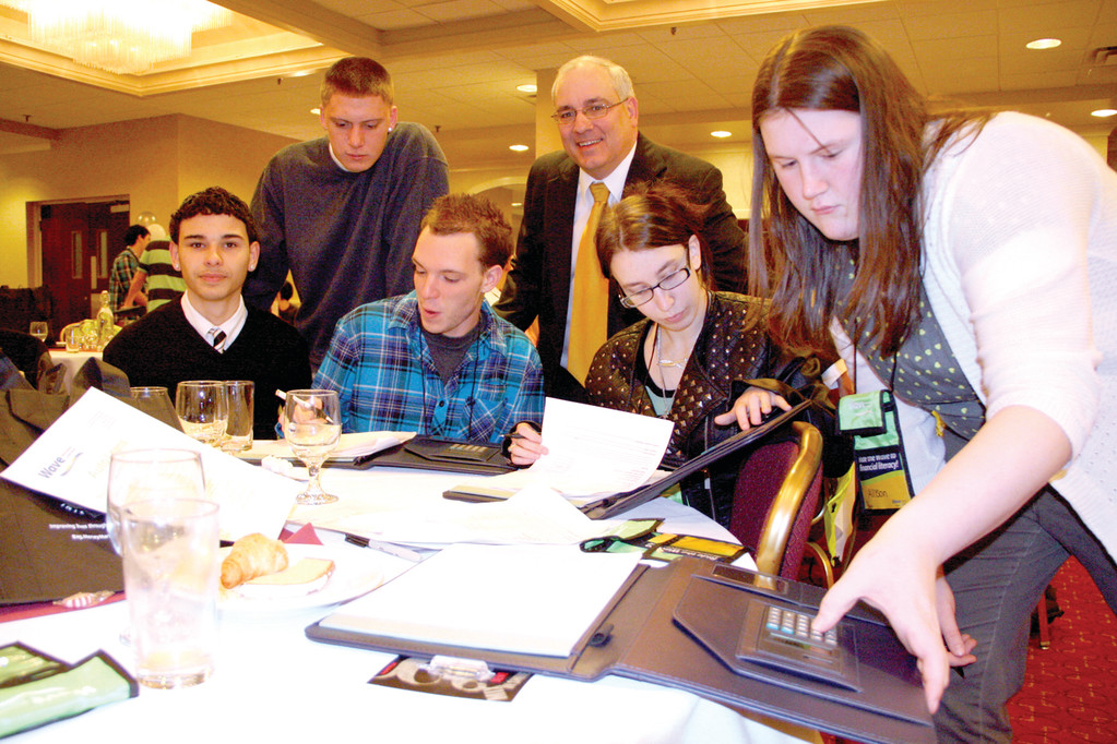 LEARNING THAT IT ALL ADDS UP: Toll Gate students Shawn Correia, Brandon Kraemer, Douglas Carani, Holly Maletesta and Allison Spencer work together to calculate their monthly budgets as Wave Credit Union President and CEO Paul Archambault looks on. Wave sponsored a financial planning workshop for the students, many of who were shocked by the cost of running a household.